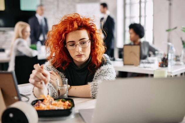 A sad woman eating salad at her desk at work
