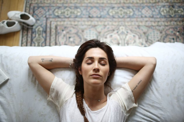 A young woman meditating in bed