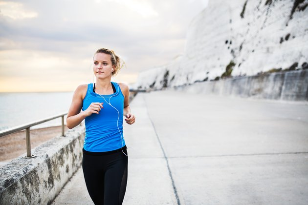 Young sporty woman runner with earphones running on the beach outside.