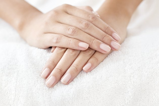 Woman with hands and nails resting on white towel