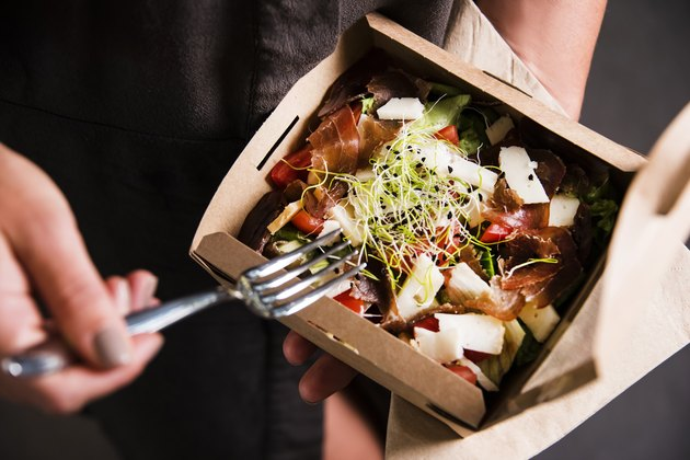 Woman's hand is holding a take away fresh salad in a lunch box.