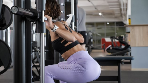 Woman is doing squats at Smith rack machine in modern fitness center
