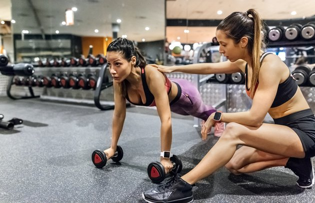 Woman with her trainer working out in gym
