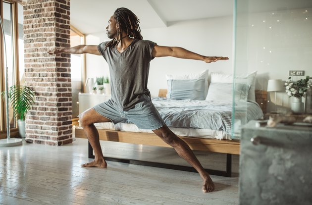 Black man in Warrior II pose in front of his bed at home