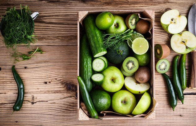Fresh sliced green vegetables and fruits in wooden crate
