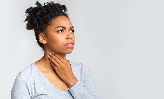 Upset woman having pain in her throat