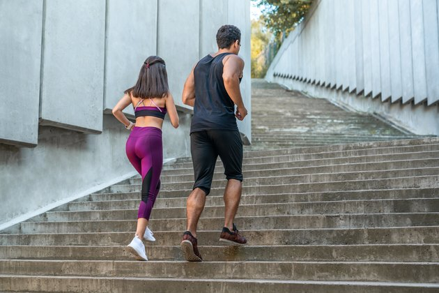 Side view of fit woman and man running up the stairs in the city