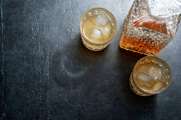 Glasses of bourbon with ice cubes on stone table. Top view