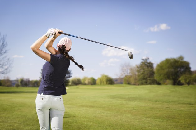 Woman golf player teeing off.
