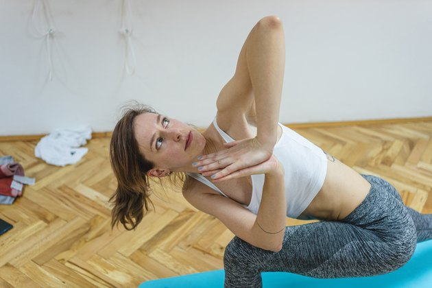 Woman in athletic clothing doing a yoga twist stretch