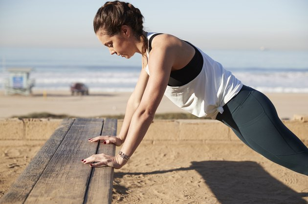 Side view of woman doing push-ups on Bench at beach