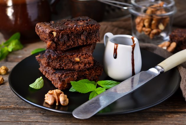 Homemade chocolate brownies with nuts, chocolate sauce and mint
