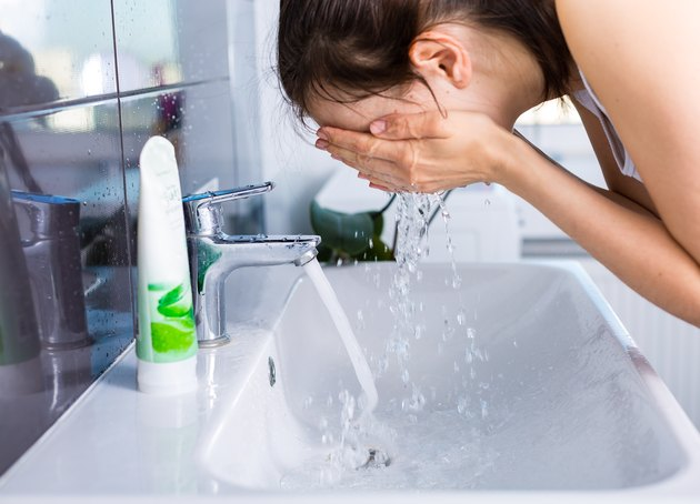 A woman washing her face in the sink