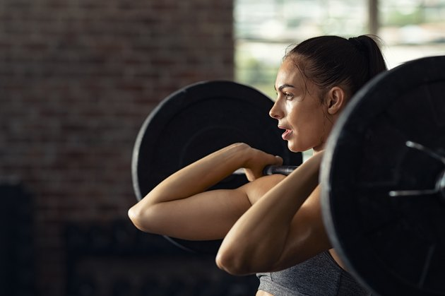 Woman doing weight lifting at cross fit gym