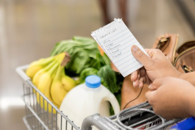 close up of woman's hands holding grocery list and cart with milk and bananas