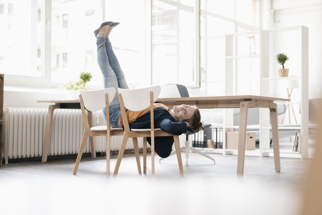 Woman doing ab exercises on a chair in a loft