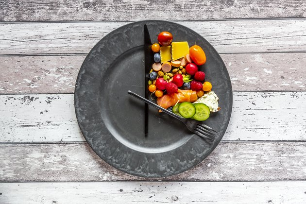 A variety of food in one corner of a plate, representing intermittent fasting