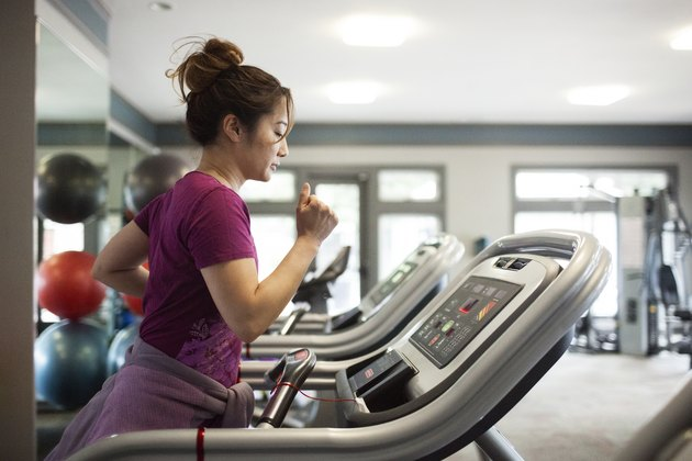 Side view of woman exercising on treadmill at gym