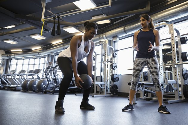 Personal trainer helping woman exercising with medicine ball in gym