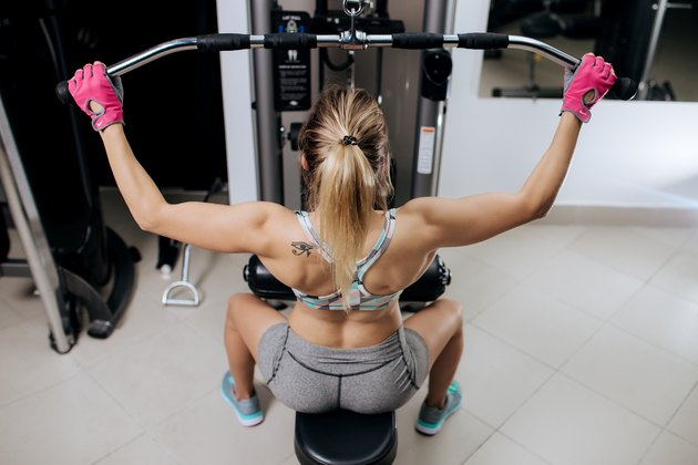 Young woman working at the lat pulldown machine in the gym. Back view.