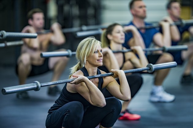 Woman performing weighted squats with a barbell