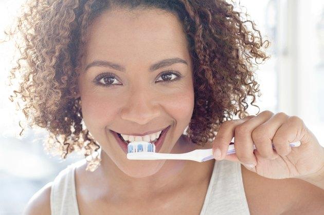 Portrait of woman brushing teeth