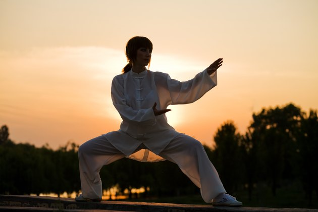 woman in white suit make's taiji chuan exercise - 4