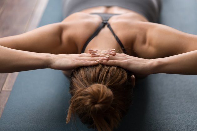 Woman practicing yoga, doing neck strengthening exercises on mat