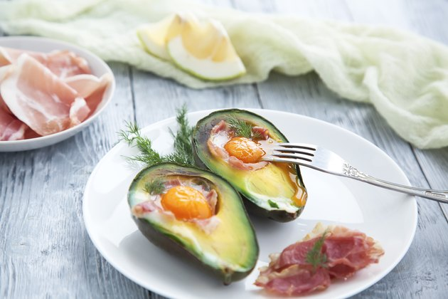 Two baked avocado halves with egg on a white saucer for low carb diet or keto diet