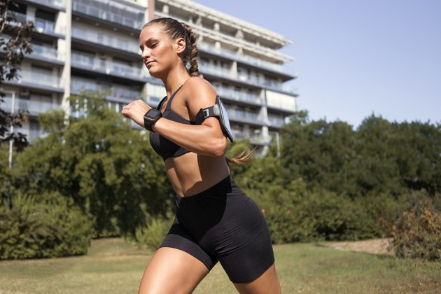 Young sportswoman running outdoors in public park