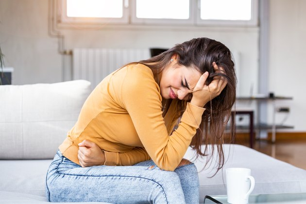 Young sick woman with hands holding pressing her crotch lower abdomen. Medical or gynecological problems, healthcare concept. Young woman suffering from abdominal pain while sitting on sofa at home