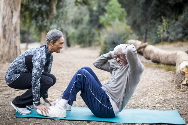 couple performing sit-ups together outside