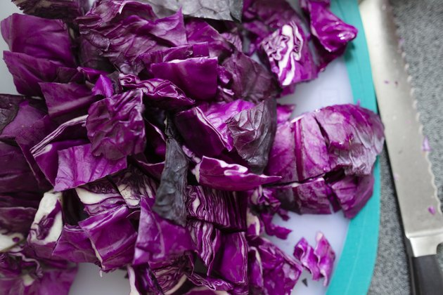 Close-up of red cabbage chopped up on cutting board next to knife