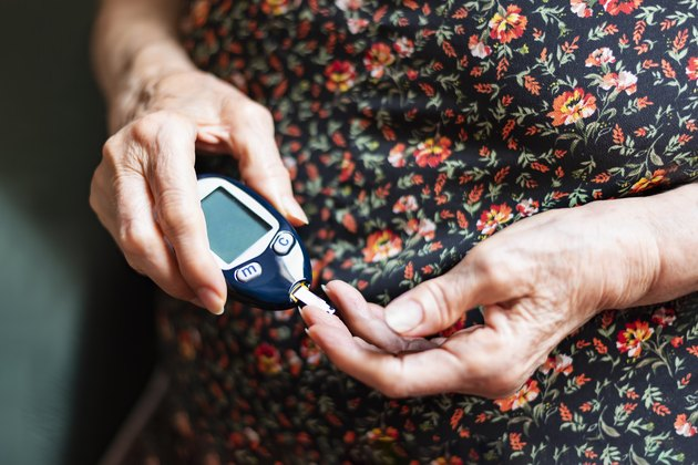 An older woman with type 2 diabetes checking her blood sugar