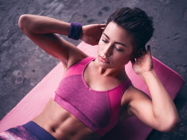 Serious woman doing sit ups on a pink exercise mat