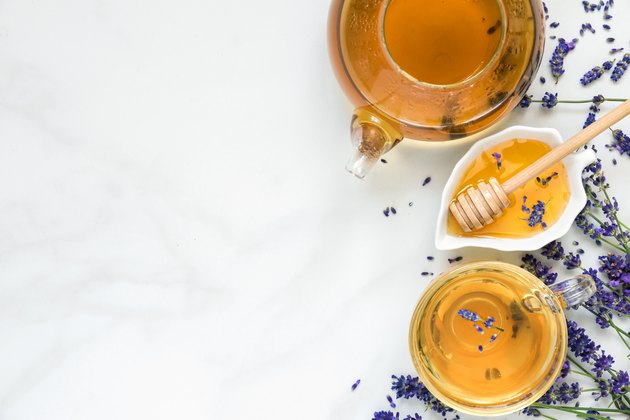 lavender tea in a cup and teapot with honey and fresh flowers over white marble table. herbal drink. top view