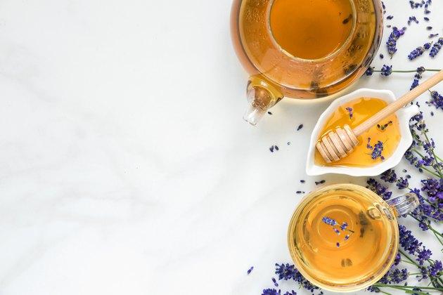 thé à la lavande dans une tasse et une théière avec du miel et des fleurs fraîches sur une table en marbre blanc. boisson à base de plantes. vue de dessus
