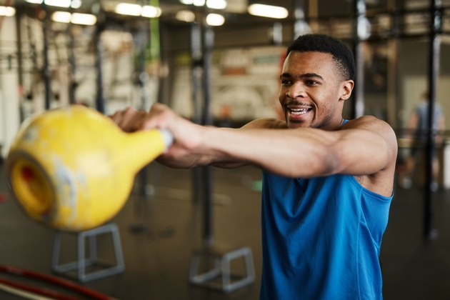 man swinging kettlebell for benefits of strength training