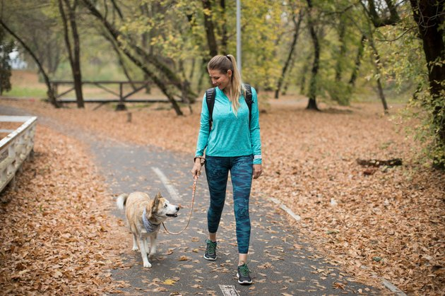 Woman walking with dog in park