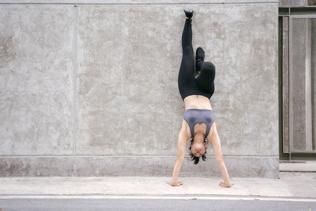 Full Length Of Woman Doing Handstand On Footpath Against Wall