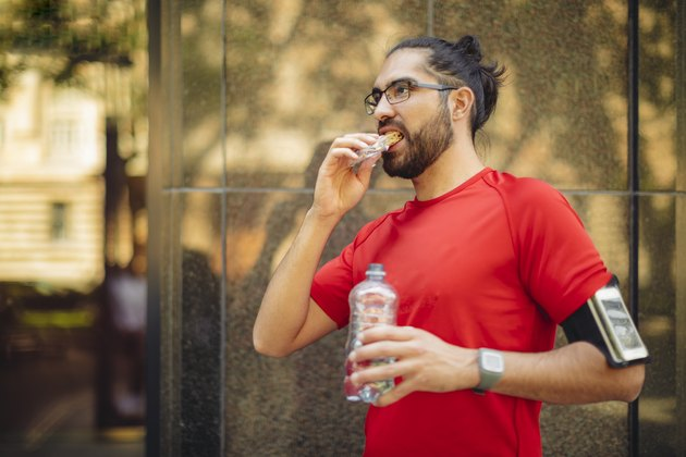 Runner having a snack during the middle of training for a marathon