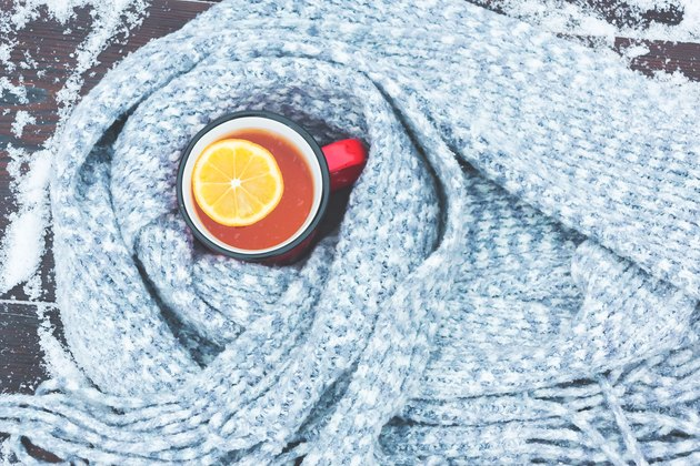 Red enameled cup of hot tea with lemon wrapped in a knitted scarf on a snowy wooden table