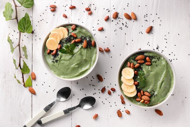 Bowls with tasty spirulina smoothie on white table
