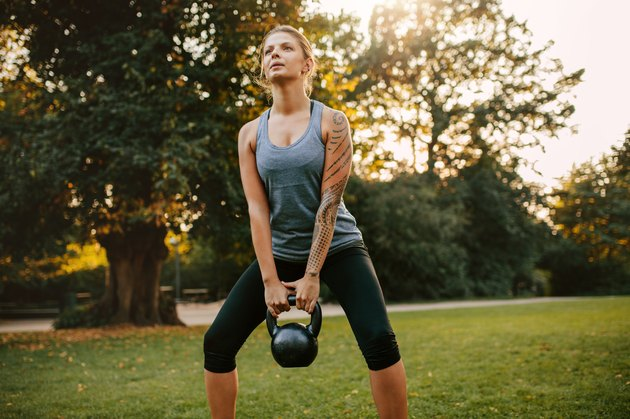 woman holding kettlebell in squat position for full-body strength workout outside