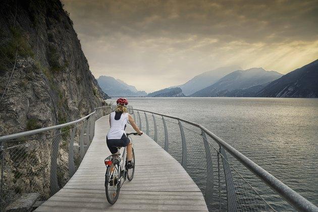 Female tour cyclist rides a modern cycle path around Lake Garda