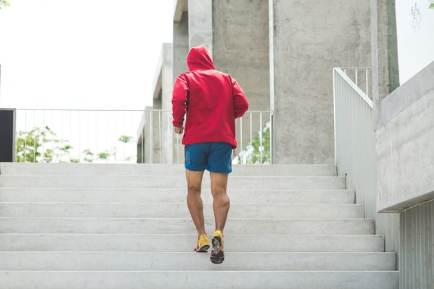 Urban athlete running upstairs. Sporty man working out outside and climbing stairs.