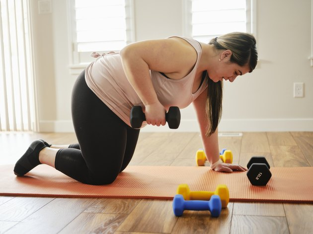 woman doing a dumbbells tricpes kickbacks exercise on a coral exercise mat at home
