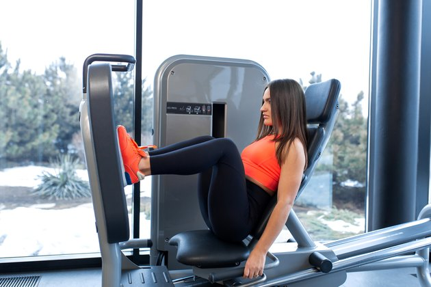 Slim smiling woman using a leg press machine and placing her legs on the platform