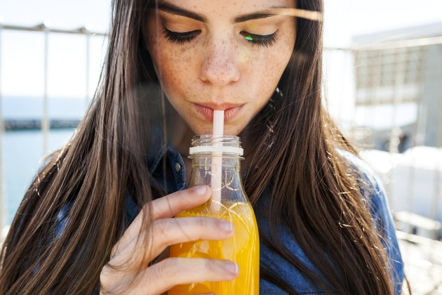 Young woman with freckles drinking orange fruit juice