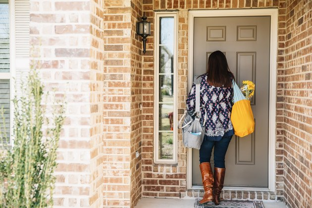 Hispanic woman opening front door, returning home from grocery store